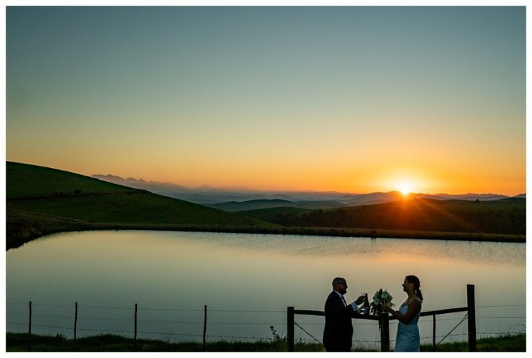 the bridal couple drinks a glass of Champaign as the sun sets behind them