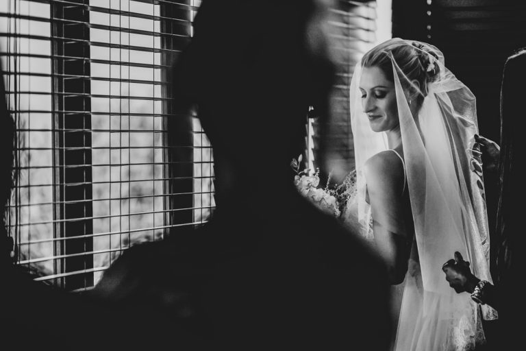 a black and white photo of the bride putting her veil on
