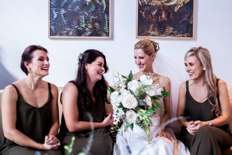 the bride and her bridesmaids share a comical moment