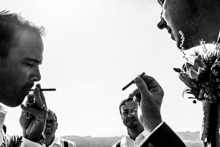 the groom shares a cigar with his groomsmen