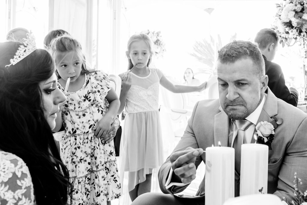emotional groom lighting a candle for his diseased mother while kids look on