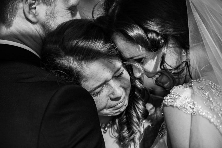 Beautiful Wedding Photos by Christelle Rall of a daughter hugging her parents just after they got married.