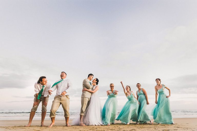 A bridal party having fun on the beach with different funny poses and belly laughs.