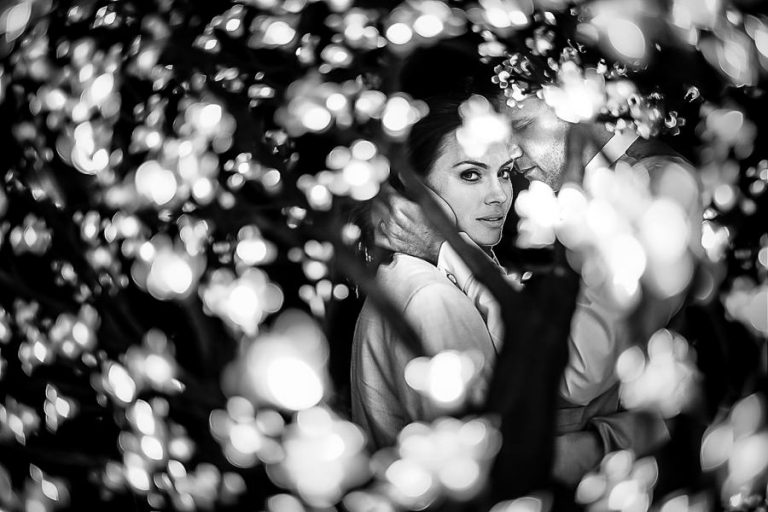 A night time portrait of the bride and groom looking through a tree of lights.