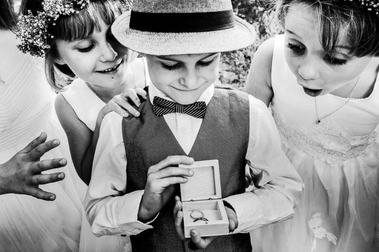 The ring bearer and flower girls kids admiring the ring set with precious facial expressions.