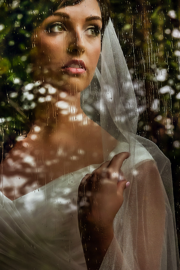 Beautiful Wedding Photos, as photographed by Christelle Rall like this classic bridal portrait looking at the rain from within a window.