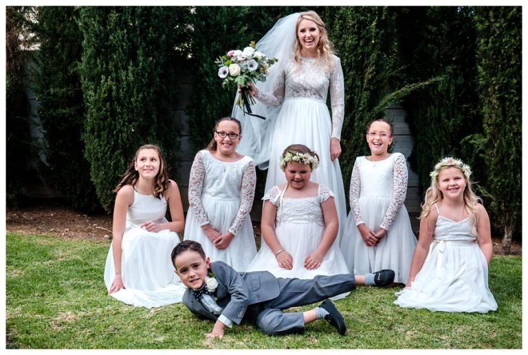 the bride and her flower girls have some fun for the photos