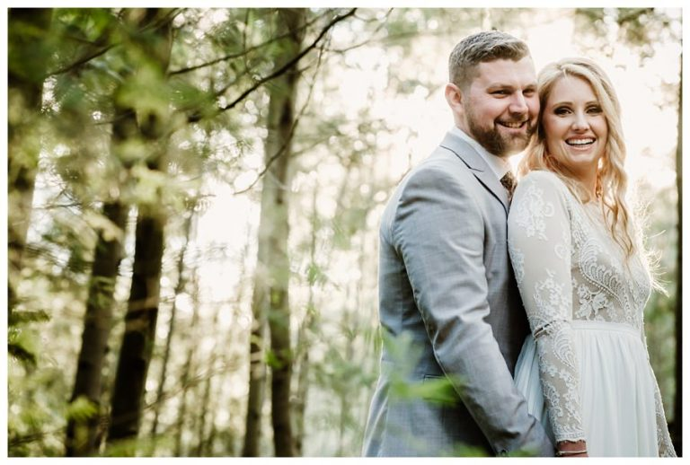 a classic wedding portrait of the newlyweds in the forest