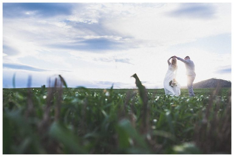 the couple do a quick dance in the farmlands as the sun sets