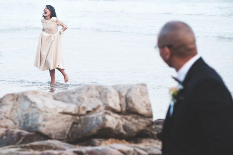 the bride reacting to the cold water on the beach