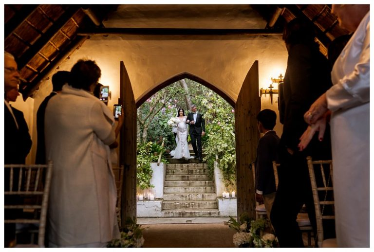 the father and the bride walks out of the forest towards the wedding chapel