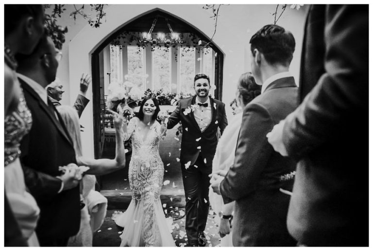 the bride and groom are being showered by rose petals as they emerge from their wedding ceremony