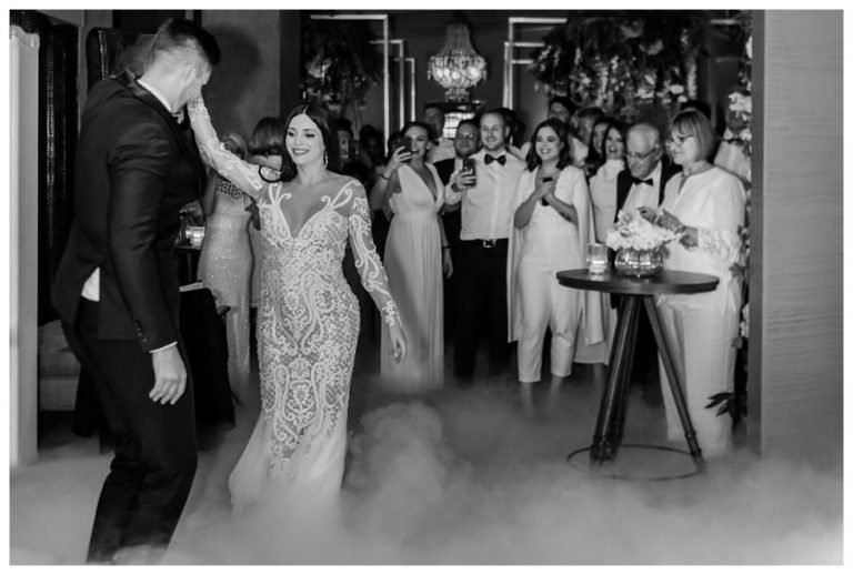 the bride and groom opens the dance floor as the wedding guests look on
