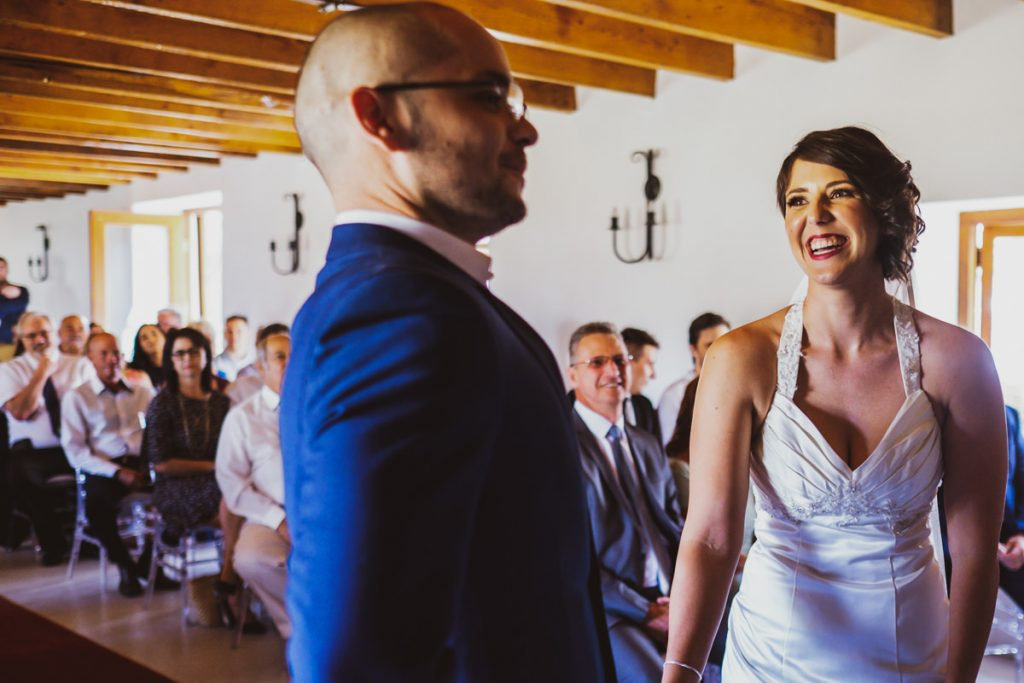 The groom takes a deep breath as the bride laughs during their wedding ceremony