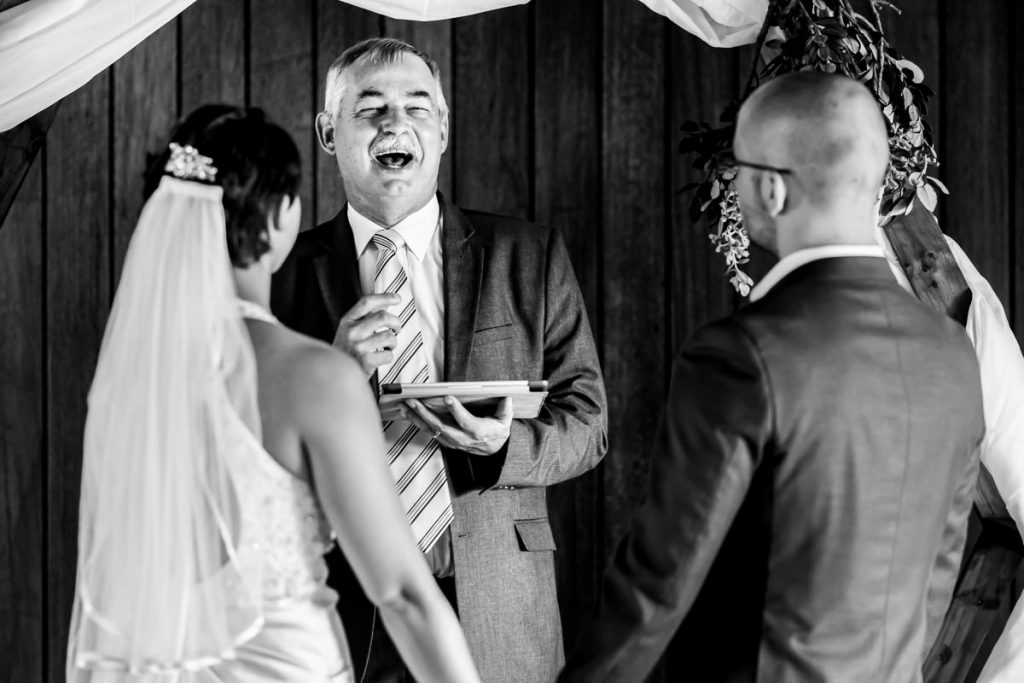 The wedding officiant makes a joke during the wedding ceremony