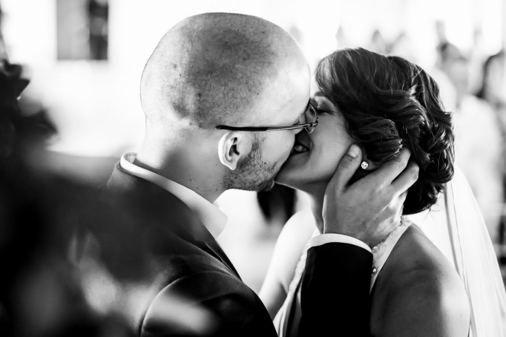 The bride and groom give their first kiss as mr and mrs