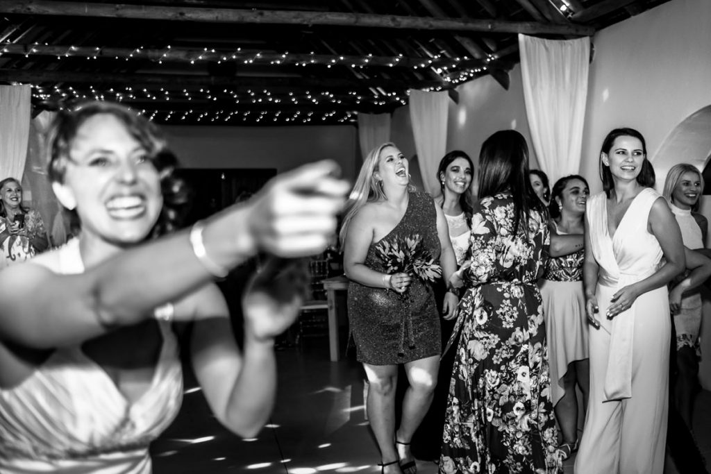 the bride reacts to a wedding guest catching the flower bouquet