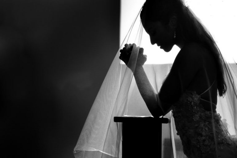 a silhouette image of a bride praying in church