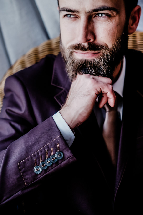 a portrait of a groom with a beard