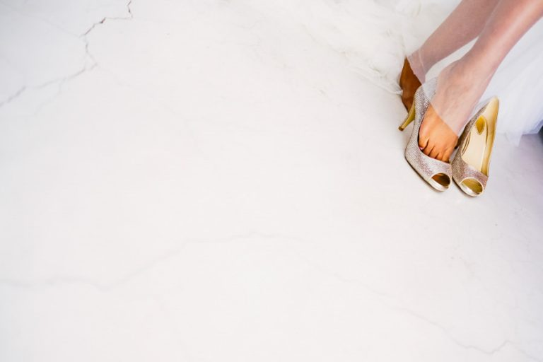 a fine art photo of the bride putting her gold shoes on