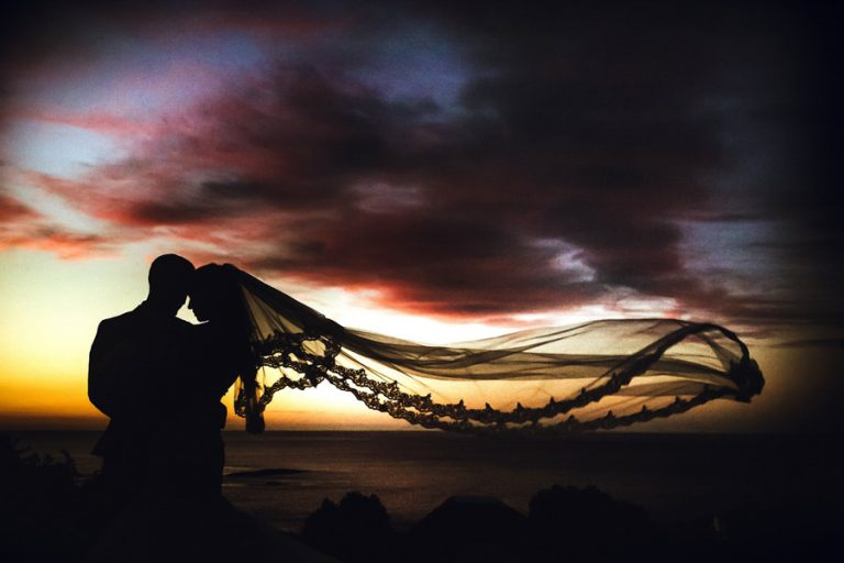 a silhouette photo of the bride and groom using the sunset