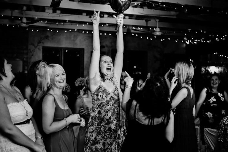 a wedding guest reacts after catching the wedding bouquet