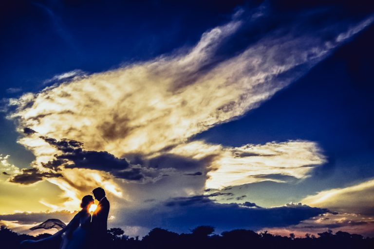a silhouette photo of the bride and groom with clouds like an angel