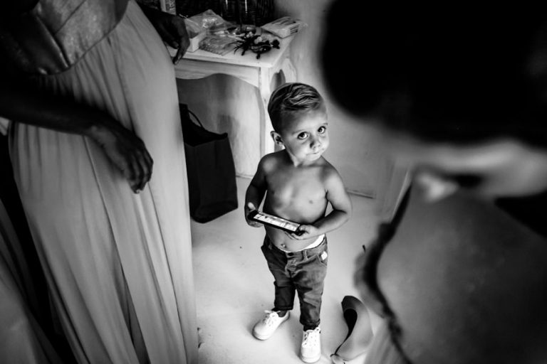 the page boy looking at the bride getting dressed