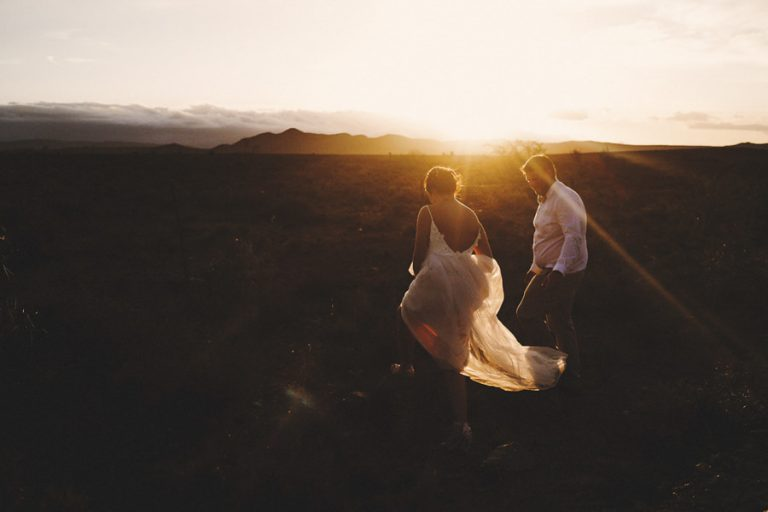 the bride and groom walk in the field with a beautiful sunset