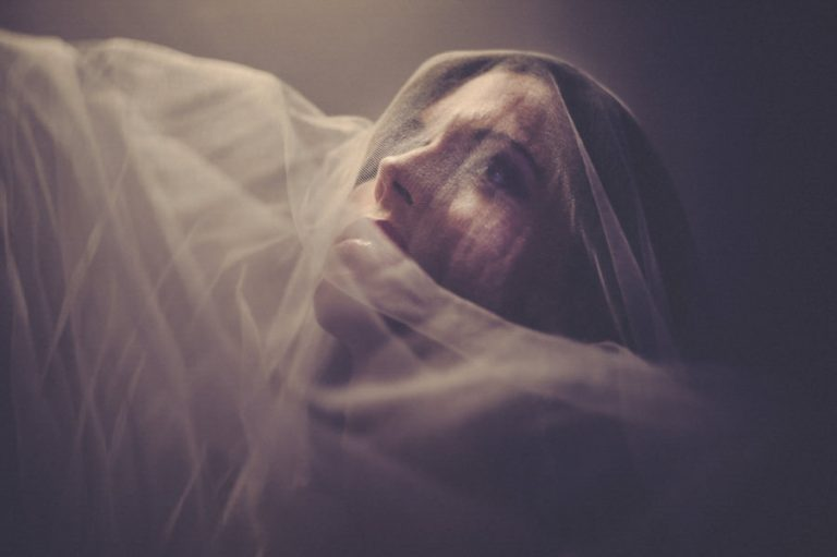 a soft bride portrait using artificial light and her veil