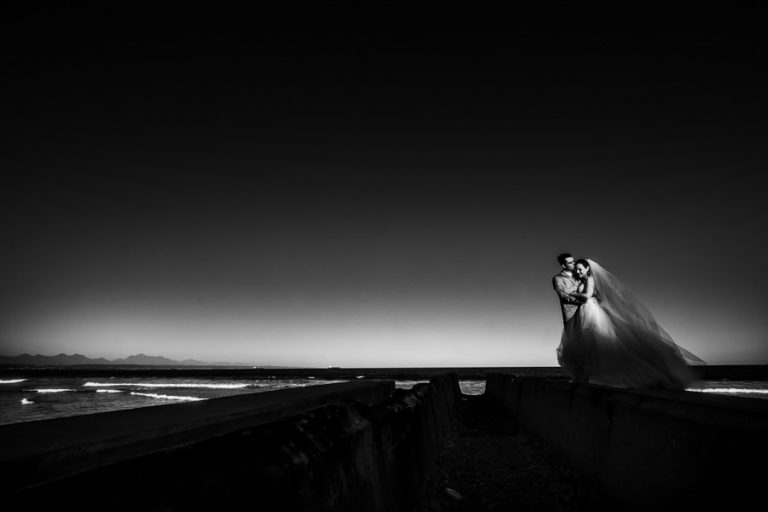 a black and white photo of the newlyweds kissing with a sun streak