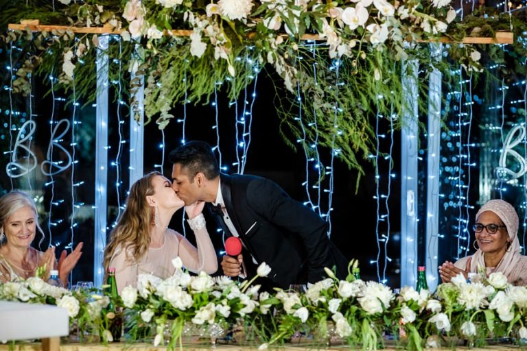 a quick kiss between bride and groom during the wedding speeches at Belair Wedding venue