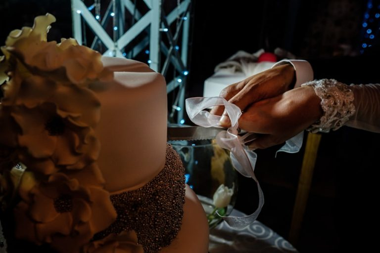 a close up of the cutting of the cake at Belair wedding venue