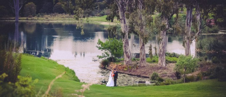 a wide photo of the newlyweds with a dam in the background