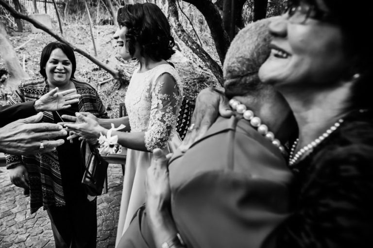 the mothers embrace as the bride and a wedding guest reacts