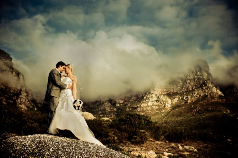 the bridal couple in front of a majestic mountain range