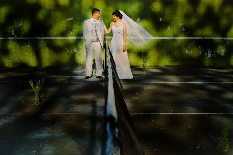 a funny moment between the newlyweds on a dilapidated tennis court