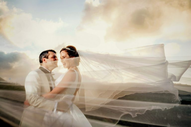 bride and groom laughing as the veil flows in the wind