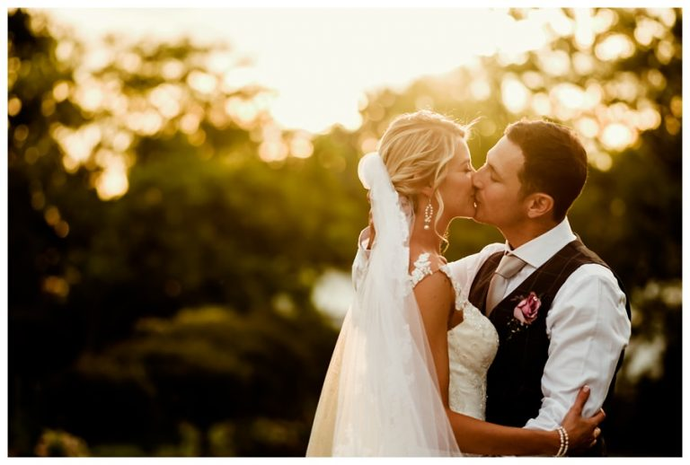 the bridal couple kissing with beautiful natural light