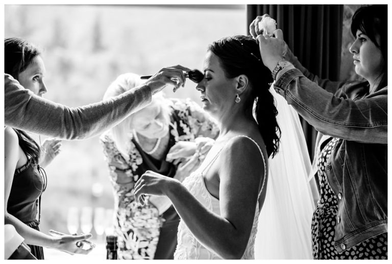 lots of hands helping the bride getting ready