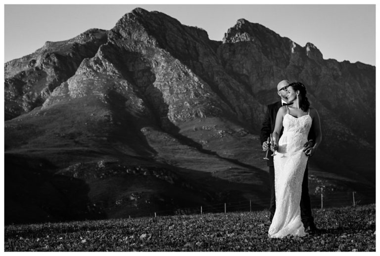 a black and white photo of the bridal couple in front of a mountain
