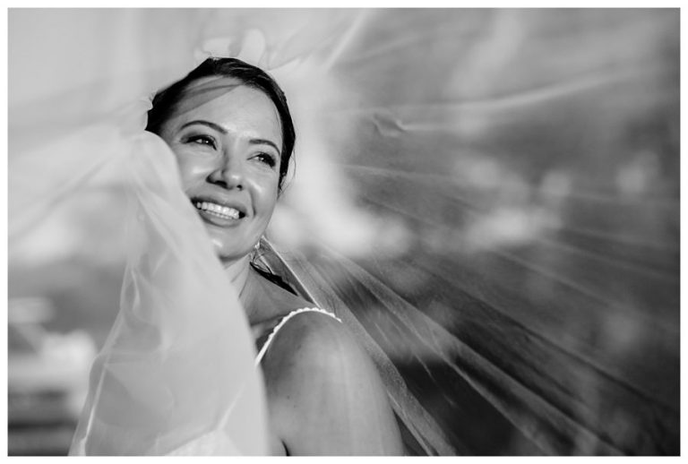 a black and white photo of the bride with her veil