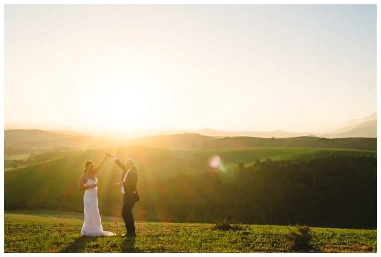 the couple do a dance move in the gorgeous sunset light