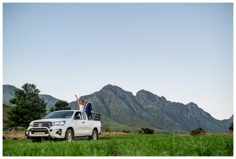 the couple on the back of a bakkie as their wedding transport