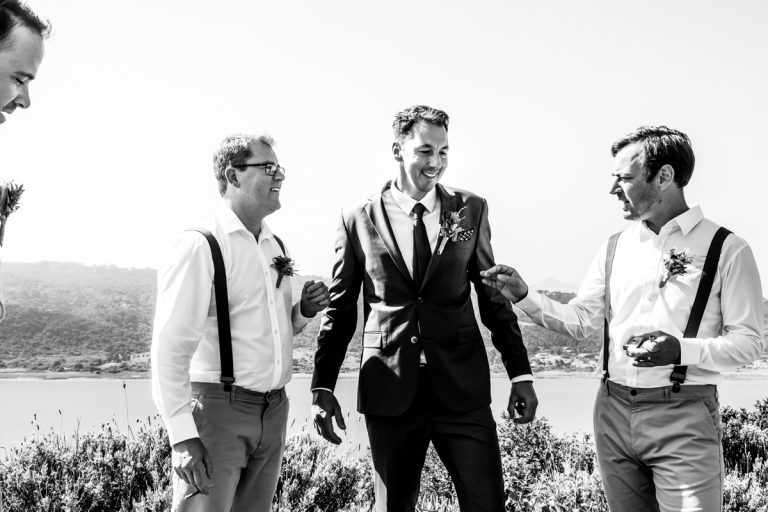 the groom and his groomsmen sharing a cigarette before the wedding