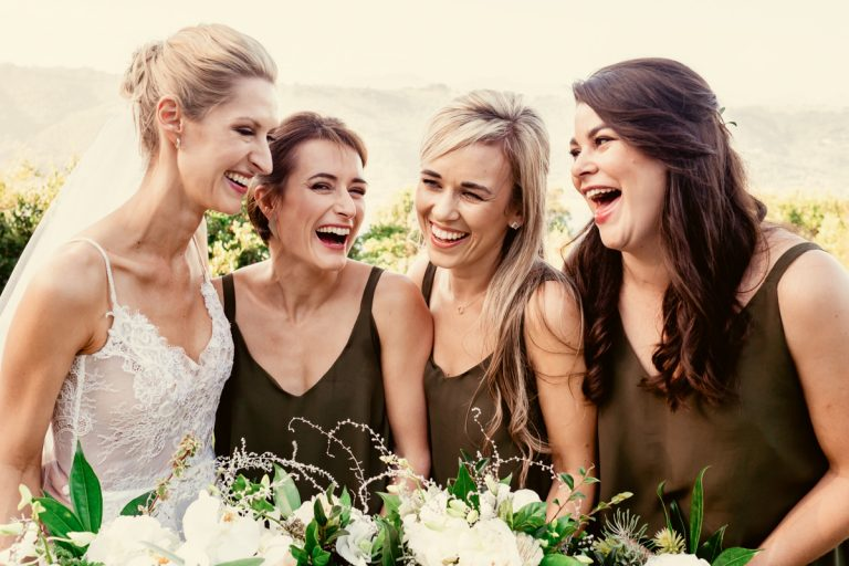 the bride and her bridesmaids shares a comical moment