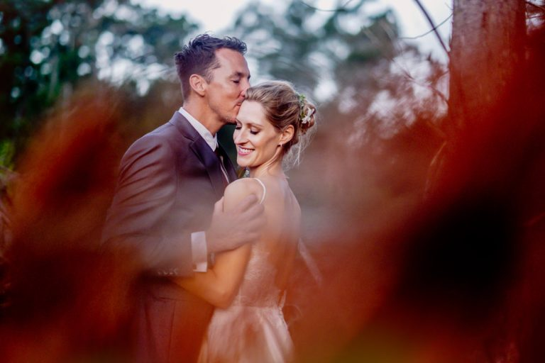 a colourful photo of the groom kissing his bride