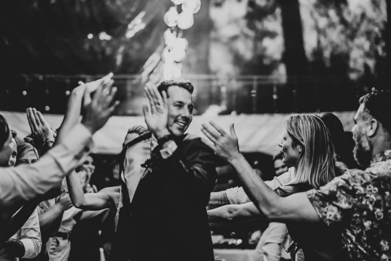 the groom gives high fives as they walk through their guests at the wedding reception