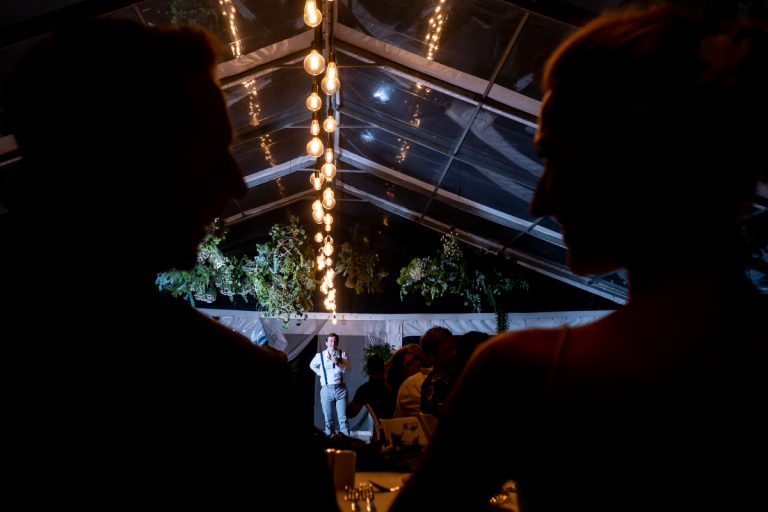 the bride and groom shares a look while the best man is doing his speech