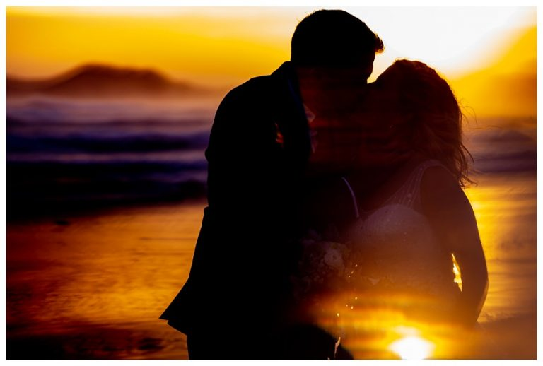 a creative silhouette of the bride and groom kissing